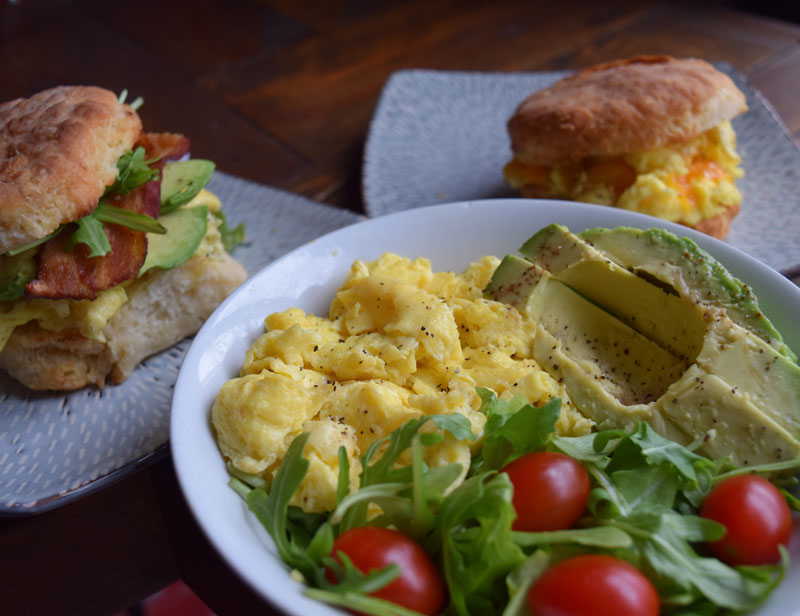breakfast bowl with scrambled eggs, tomatoes, and avacado sitting on a table in front of two breakfast biscuits
