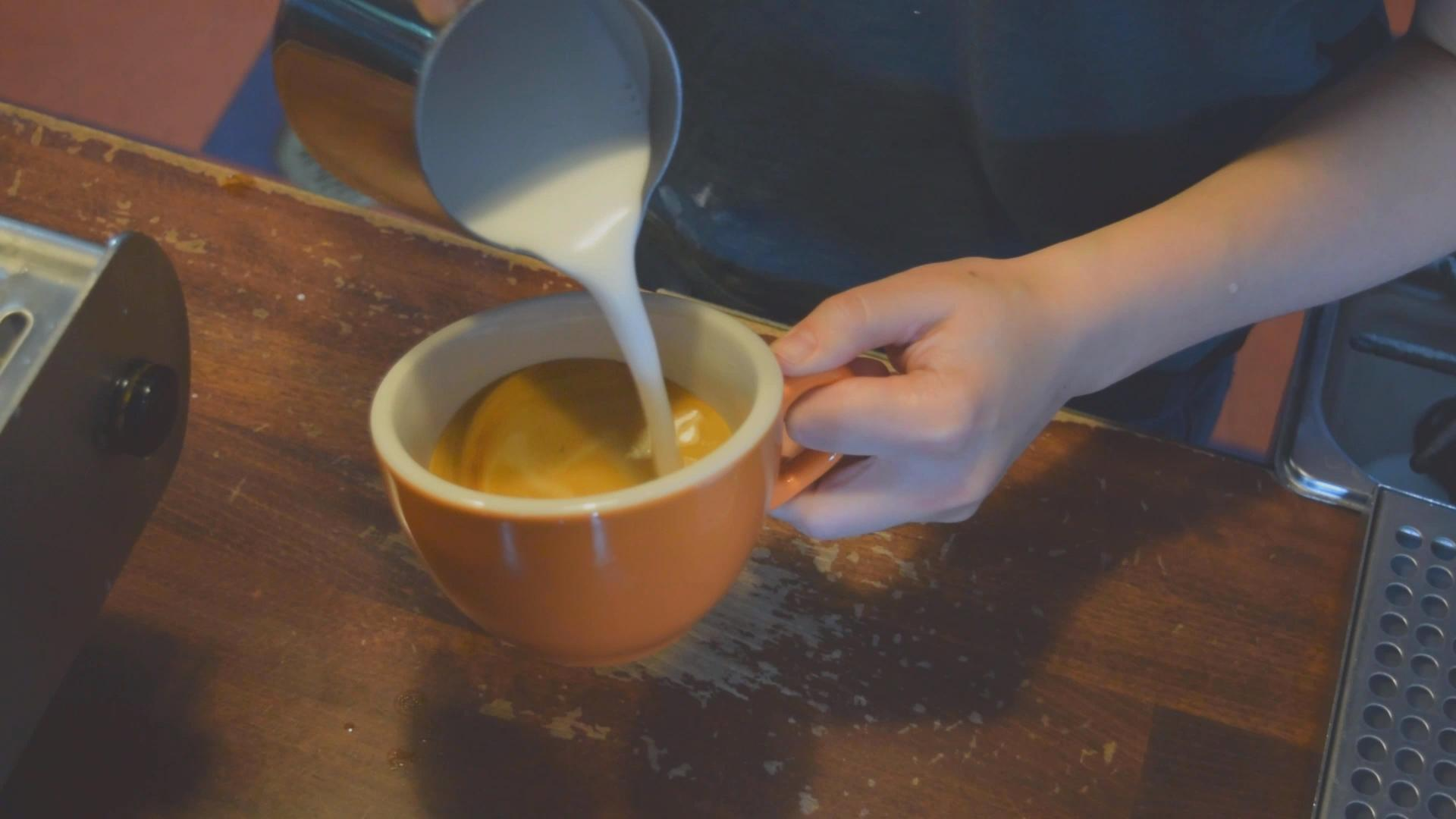 barista pouring milk into coffee in an orange coffee cup